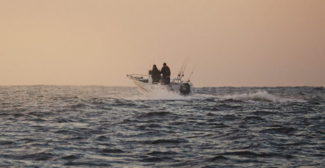 Offshore fishing boat cruising in the Pacific Ocean at sunset